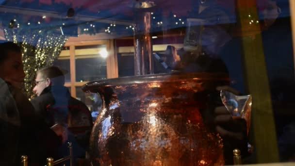 people working in stall of Christmas market Berlin cooking Feuerzangenbowle