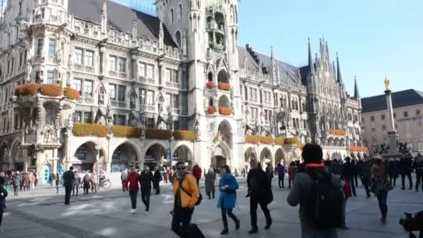 People walking across Marienplatz in Munich. In background town hall. Camera pan up to top of Town hall.