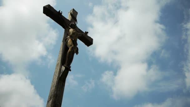 Kříž s Ježíšem proti obloze