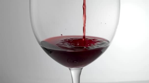 Slow motion shot of red wine being poured into glass