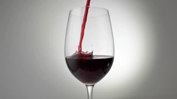 Zpomalený záběr červeného vína, které se nalévá do skla