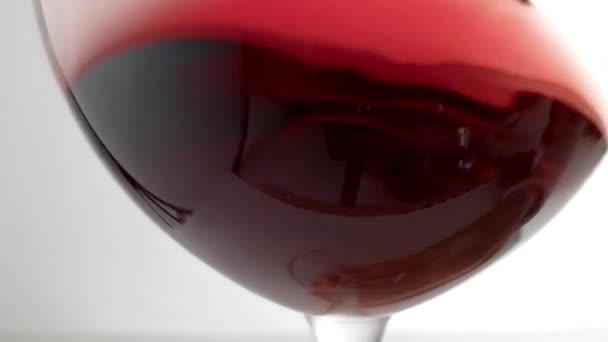 Zpomalený záběr vířícího červeného vína kolem skla