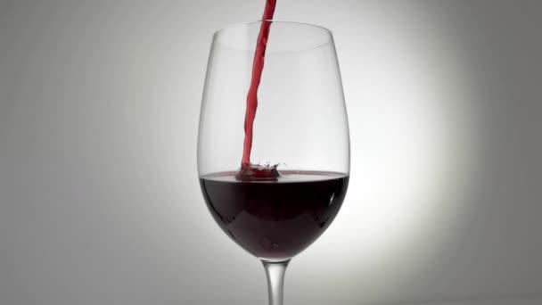 Zpomalený film s červeným vínem nalévaným do skla