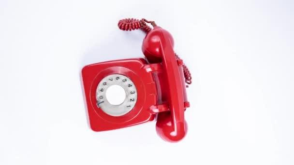 Červený klasický rotační telefon oddalující
