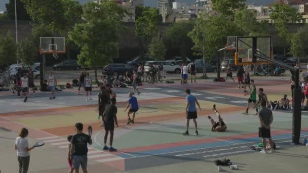 Mladí dospělí hrají basketbal venku