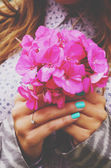 Fotografie Stylish lady holding bunch of pink flowers in her hands with tea
