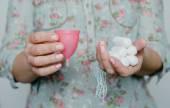 Fotografie Frau hält Tampons und Menstruationstasse in Händen