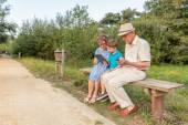 Fotografie Enkel und Oma verwenden eines Tablet im freien
