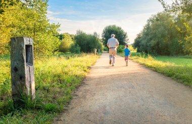 Senior man and happy child running outdoors