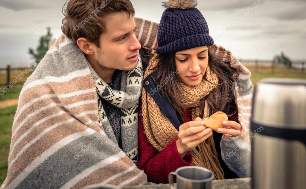 Young couple under blanket eating muffin outdoors in a cold day