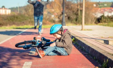 Boy with knee injury after falling off to bicycle