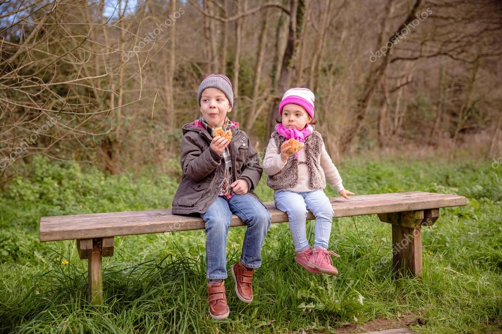 Cute boy and little girl eating muffins sitting on bench