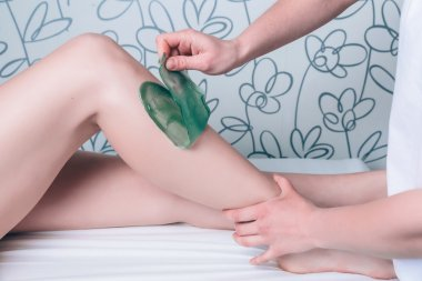 Beautician hands doing depilation in woman legs with hot wax