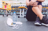 Fotografie Sporty woman sitting with dumbbells, water and smartphone in gym floor