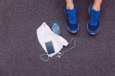 Man legs with sneakers, towel, water and smartphone in gym floor