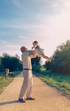 Senior man playing with baby girl outdoors