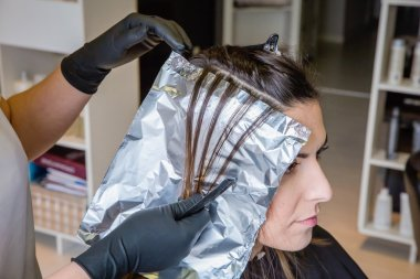 Hairdresser hands separating woman hair with aluminium foil