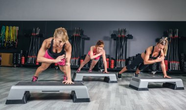 Women group training over steppers in aerobic class