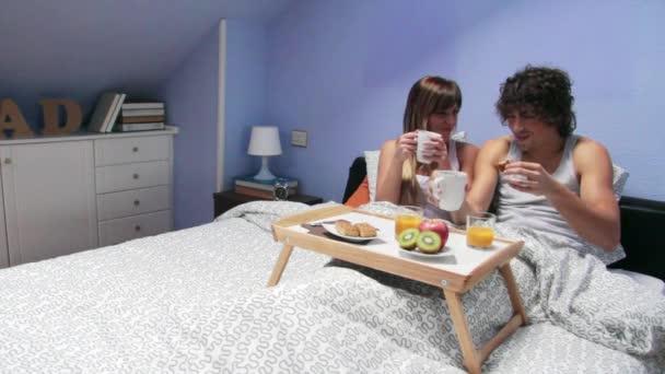 Coppia baciare e avendo la colazione nel letto servita sul vassoio