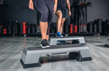 Couple legs over steppers training in aerobic class