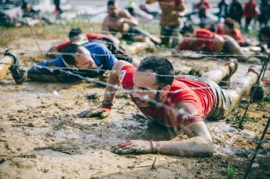 Runner crawling under barbed wire in a test of extreme obstacle race