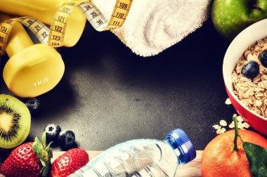Dumbbells, water bottle and fresh fruits