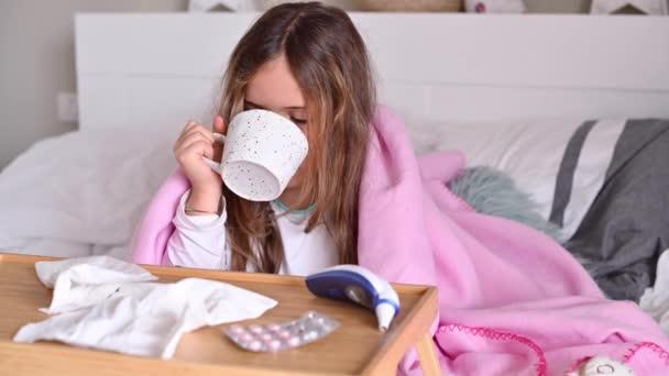 Das Kind ist krank, trinkt Tee und niest, bedeckt sein Gesicht mit einer Serviette. Ein kleines Mädchen sitzt auf dem Bett, sie ist erkältet. Das Konzept der Virus- und saisonalen Krankheiten COVID 19.