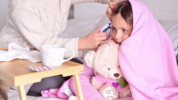 Ein kleines Mädchen schläft im Bett, sie ist erkältet, sie ist krank. Mama weckt das Baby und misst die Temperatur mit einem elektronischen Thermometer. Pflegekonzept für Viruserkrankungen