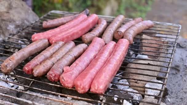 Klobásy BBQ se smaží na ohni pod širým nebem. Příprava masových uzenek na pikniku k rodinnému obědu.