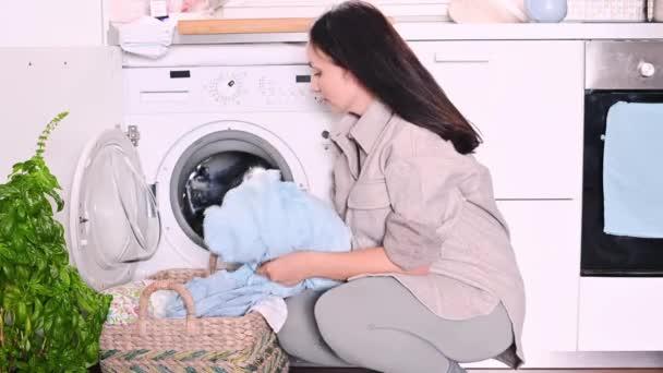 Egy fiatal, gyönyörű nő rendezgeti a mosógépben a szennyest, megszagolja és büdös. A nő megcsinálja a házi feladatát..