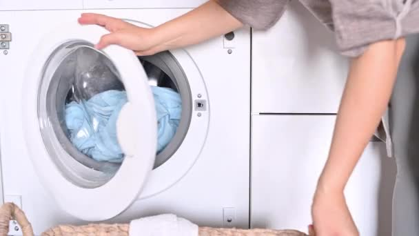 A nő beteszi a szennyest a mosógépbe a kosárból. Kezek és dob egy mosógép közelkép.