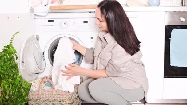 A fiatal, gyönyörű nő a kosárból a mosógépbe hajtogatja a szennyest. Egy nő házi feladatot csinál egy világos szobában..
