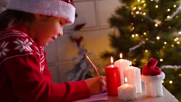 Kleines Mädchen schreibt einen Brief an den Weihnachtsmann in einem süßen, weihnachtlich dekorierten Haus. Das Kind träumt von Teenagern für das neue Jahr. Hochwertiges 4k Filmmaterial