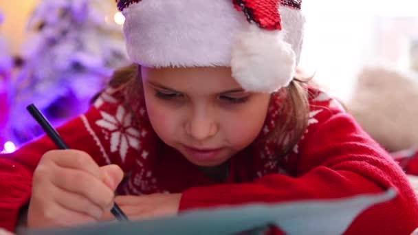 Kleines Mädchen im roten Pullover schreibt einen Brief an den Weihnachtsmann in einem weihnachtlich geschmückten Haus.