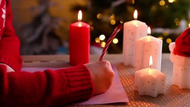 Kleines Mädchen schreibt einen Brief an den Weihnachtsmann in einem süßen, weihnachtlich dekorierten Haus.