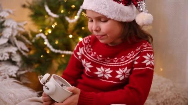 Ein kleines Mädchen mit Weihnachtsmannmütze und rotem Pullover hält einen Wecker in der Hand. Kind im Zimmer mit Christbaumgirlanden.