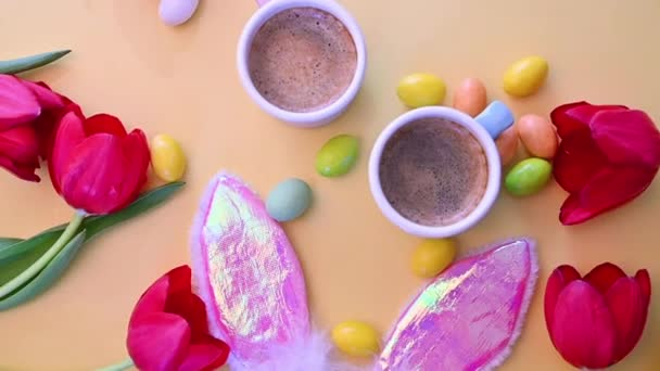 two cups of fragrant espresso and chocolate Easter eggs on a yellow background. Flowers, black coffee and sweets. View from above