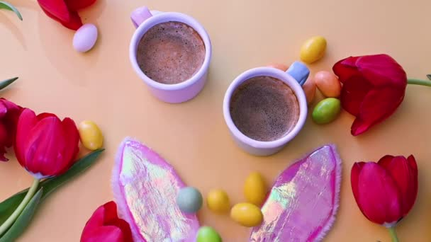 Easter holiday. two cups of fragrant espresso and chocolate Easter eggs on a yellow background. Flowers, masquerade bunny ears, black coffee and candy. View from above