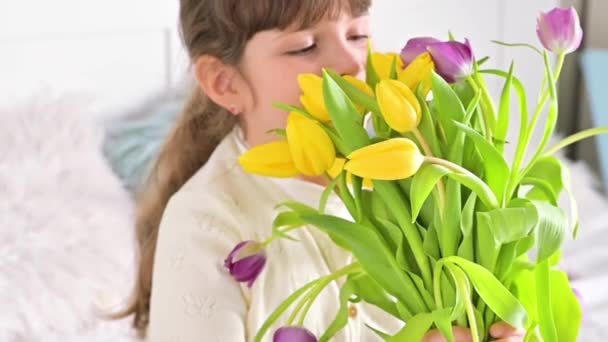 A little girl with a bouquet of bright tulips in her hands, she sniffs them and smiles. A gift for mom or grandmother on womens day. 8 March Womens Day concept.