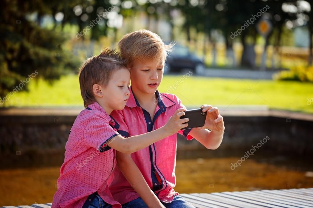 Two Children Telling Secrets And Laughing In Park
