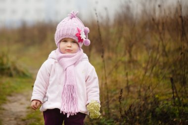 Happy baby girl in a pink hat and scarf laughs in autumn cold day