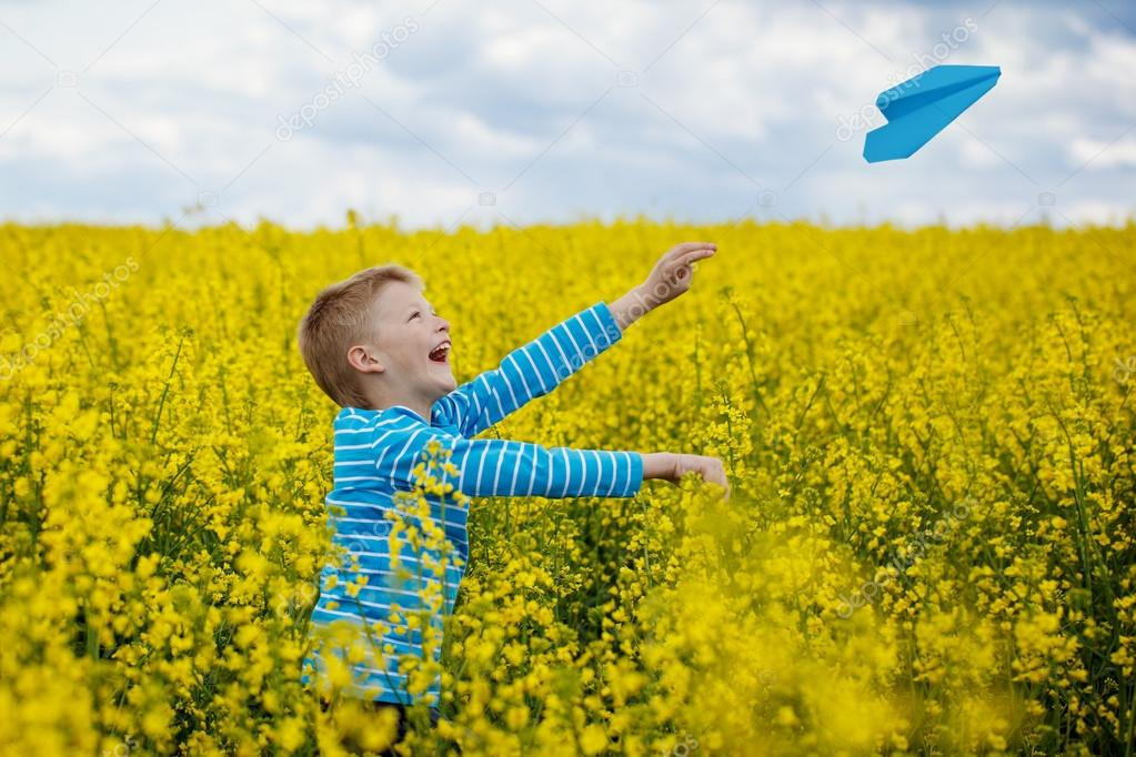 Happy boy leaning and throwing blue paper airplane on bright sun