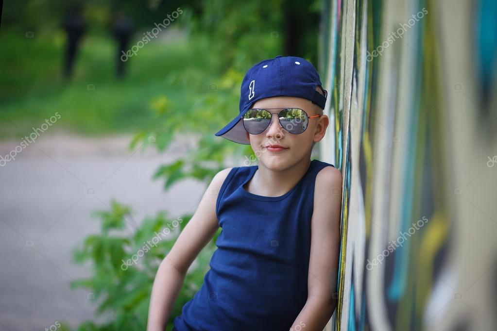 85aa0d07dd65 Fashionable little boy in sunglasses and cap.Graffiti background — Stock  Photo