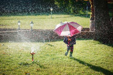 Little girl with umbrella playing in the rain. Kids play outdoor