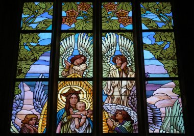 Virgin Marry surrounded by angels. Art Nouveau stained glass win