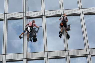Rope access workers clean windows