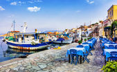 Photo traditional Greece series - Chalki island with old boats and taverna