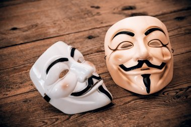Anonymous mask on wood background