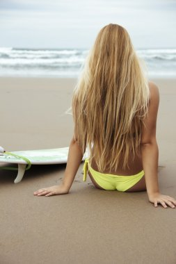 Girl with surfboard on the beach