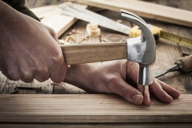 Woodworker hammer a nail